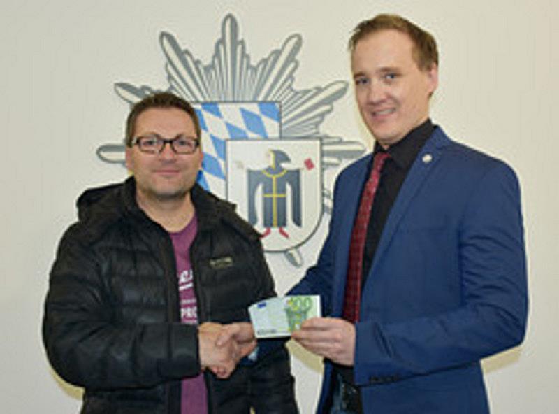 POK Ellmeier übergibt 100 Euro als Belohnung an aufmerksamen Nachbarn, der einen Rentner davor bewahrt hat, 2.620 Euro an Zirkus-Trickbetrüger zu verlieren Quelle Foto: Polizei München
